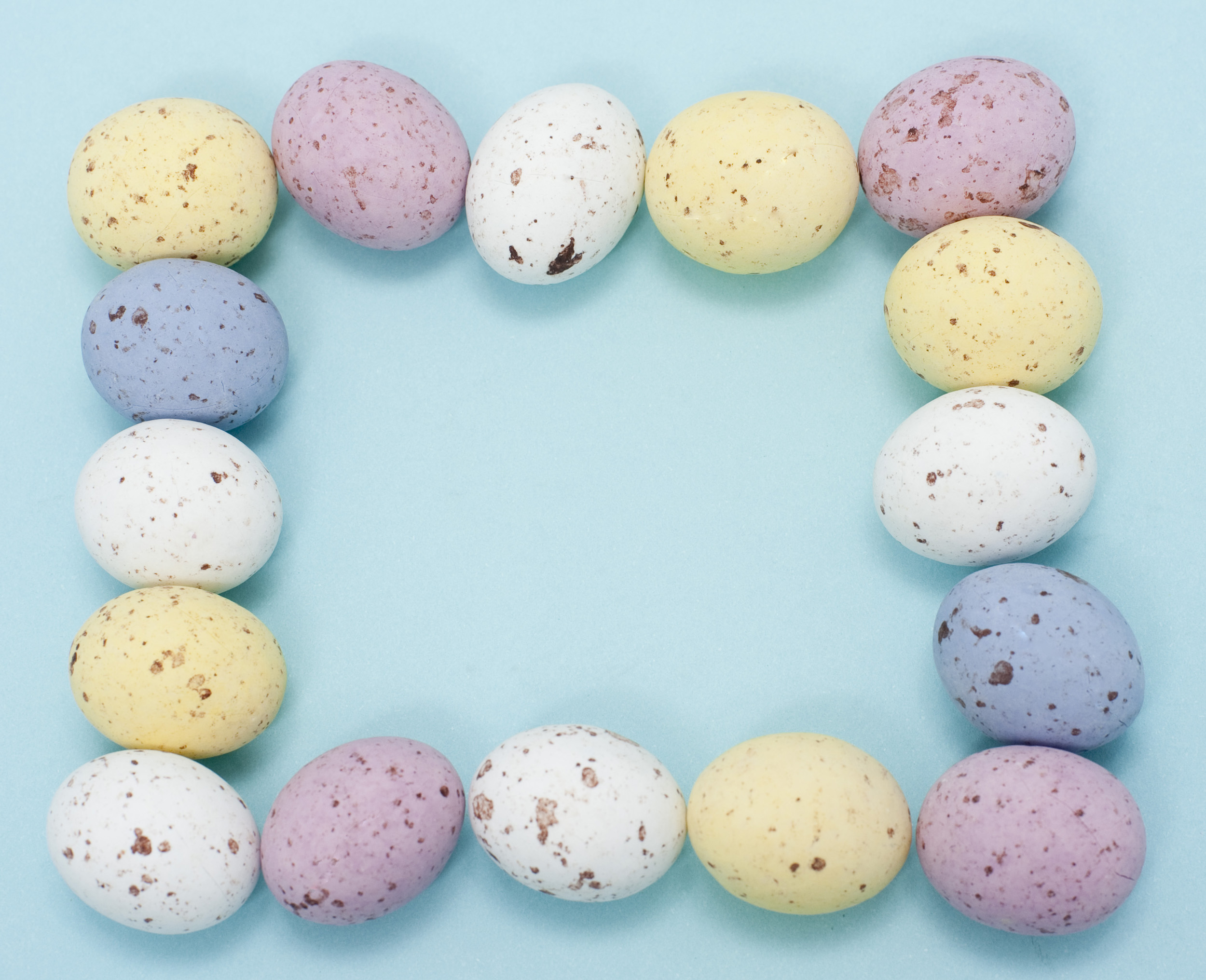 Frame with blank copyspace bordered by speckled candy Easter eggs in pastel shades of pink, yellow, white and blue, blue background.