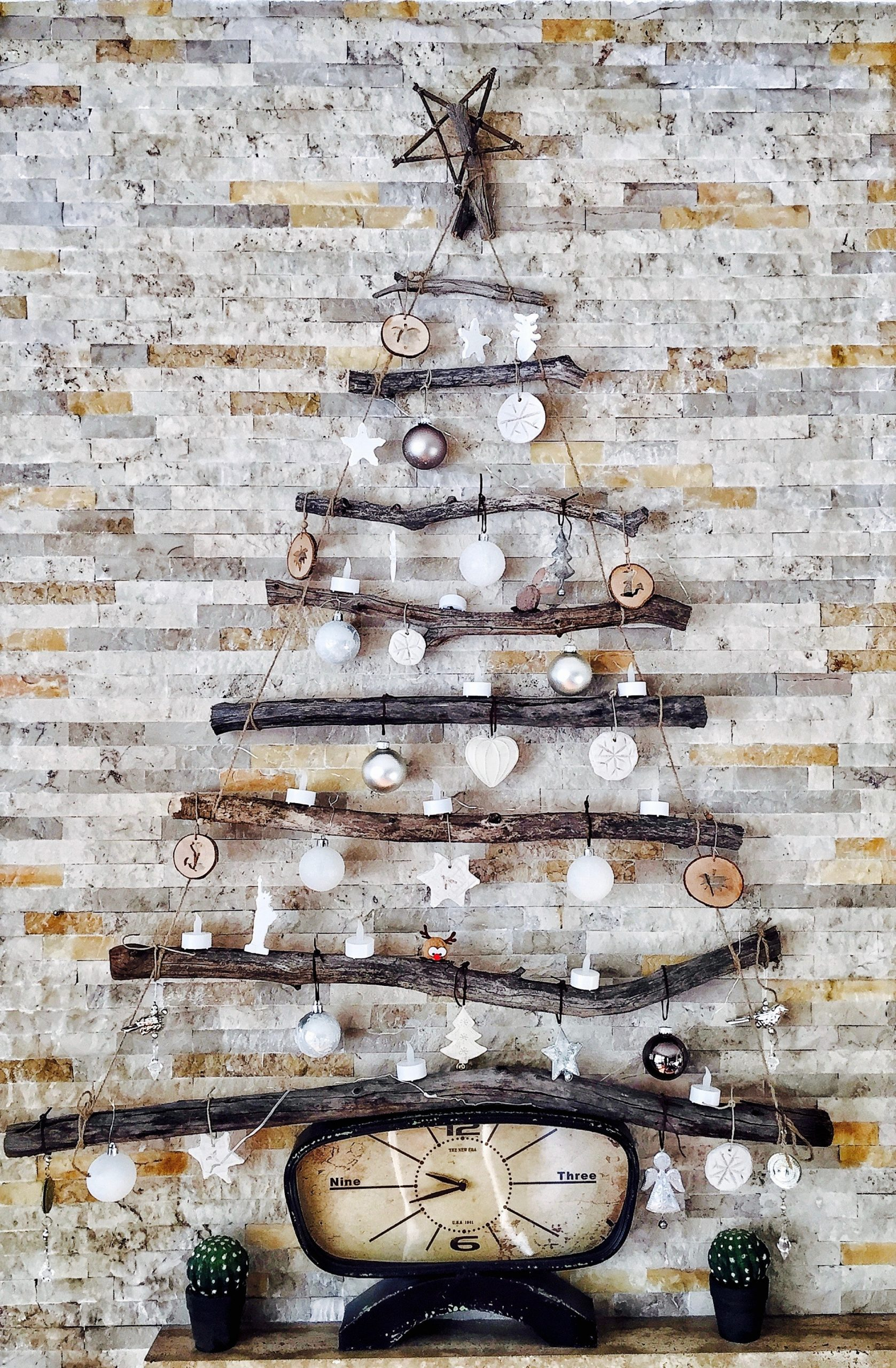 A Christmas wall décor using tree branches and decorative elements.