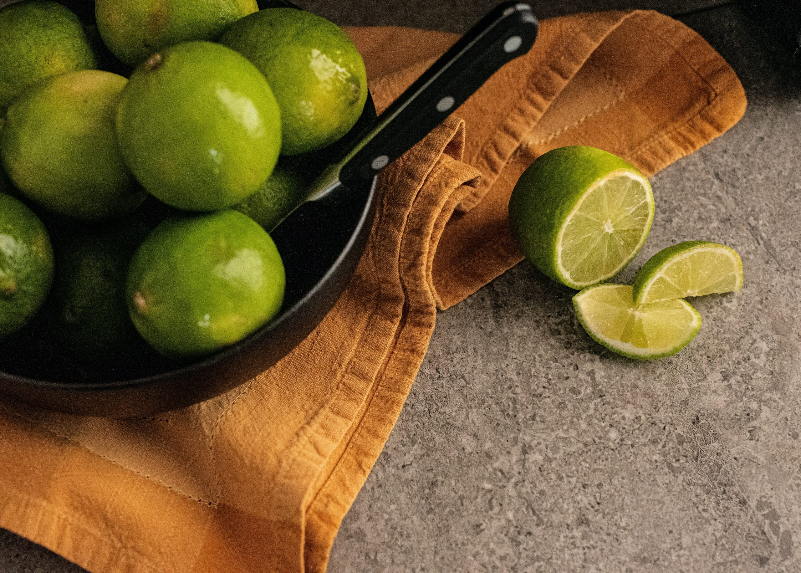 A black pan containing lemons and a knife placed on a yellowish brown cloth with cut pieces of lemon on the side