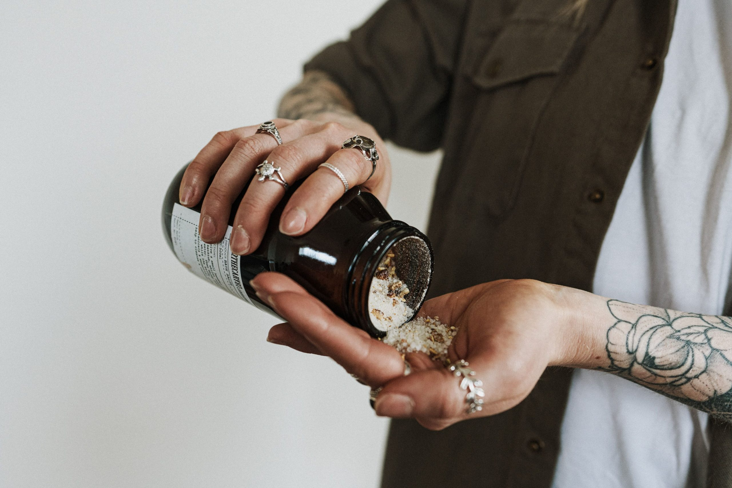 An open bottle of flavored salt being poured by someone onto their left palm set against a white background.