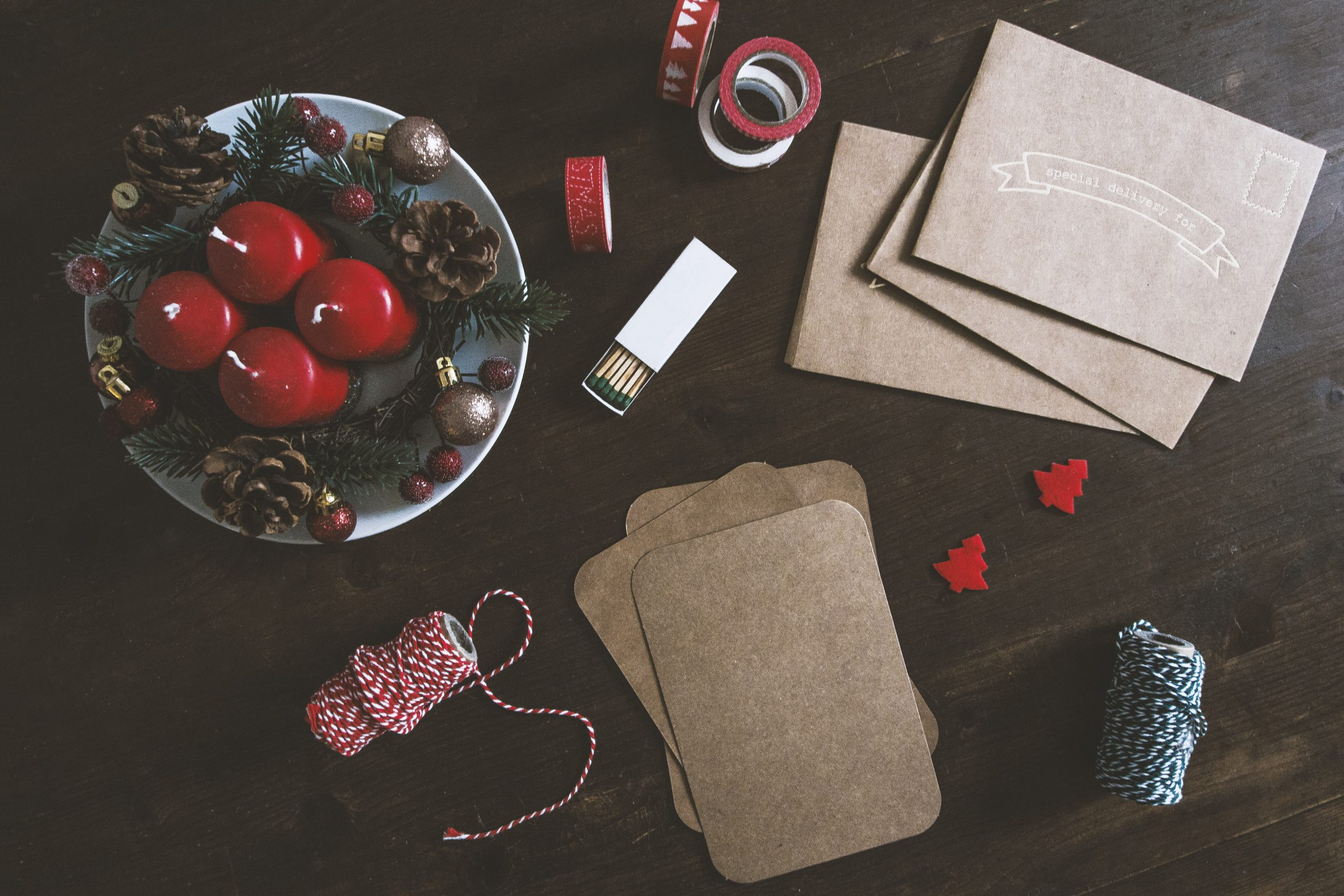 A brown table decorated with two rolls of thread, brown envelops, brown pads, designer tape, two small red Christmas trees, an open matchbox, and a plate with four red candles, pine cones, berries, and baubles.