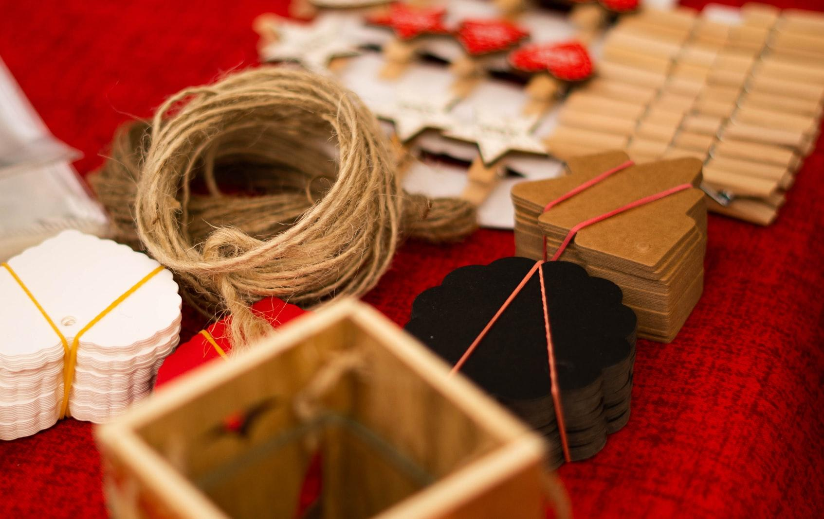 Different kinds of art and craft materials placed on a red fabric.