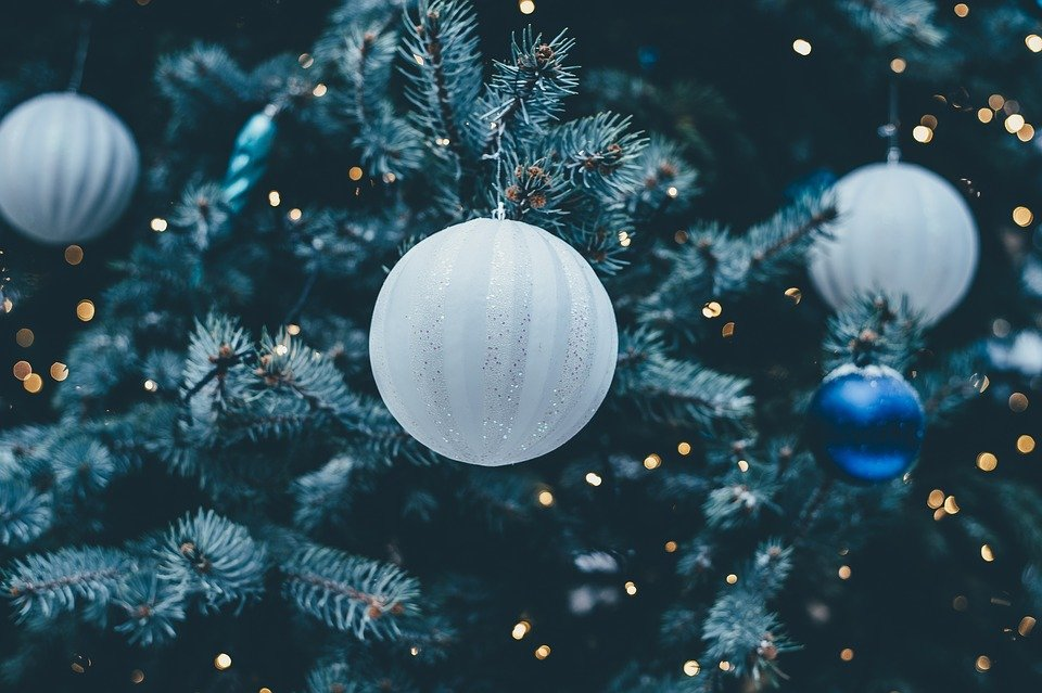 Blue and white baubles hanging from a Christmas tree.