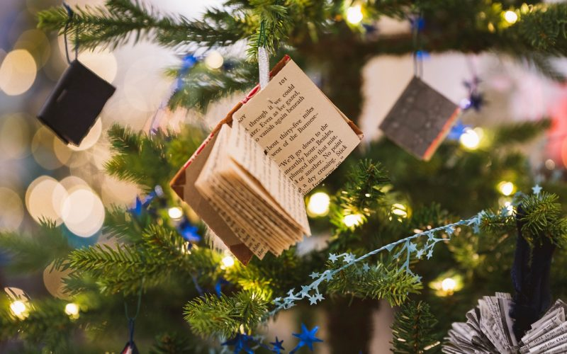 A miniature book decoration hanging from a Christmas tree.