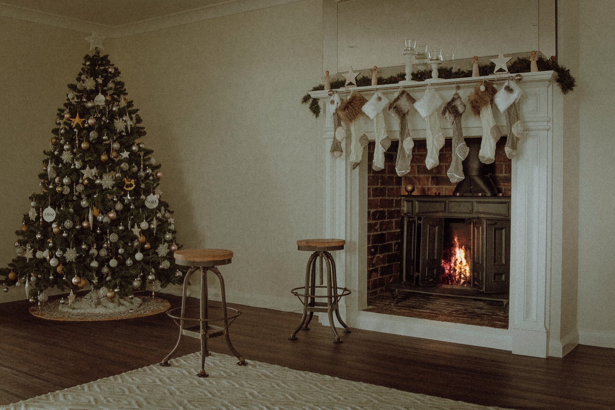 A Christmas tree featuring white decorative elements in a white room with a fireplace.