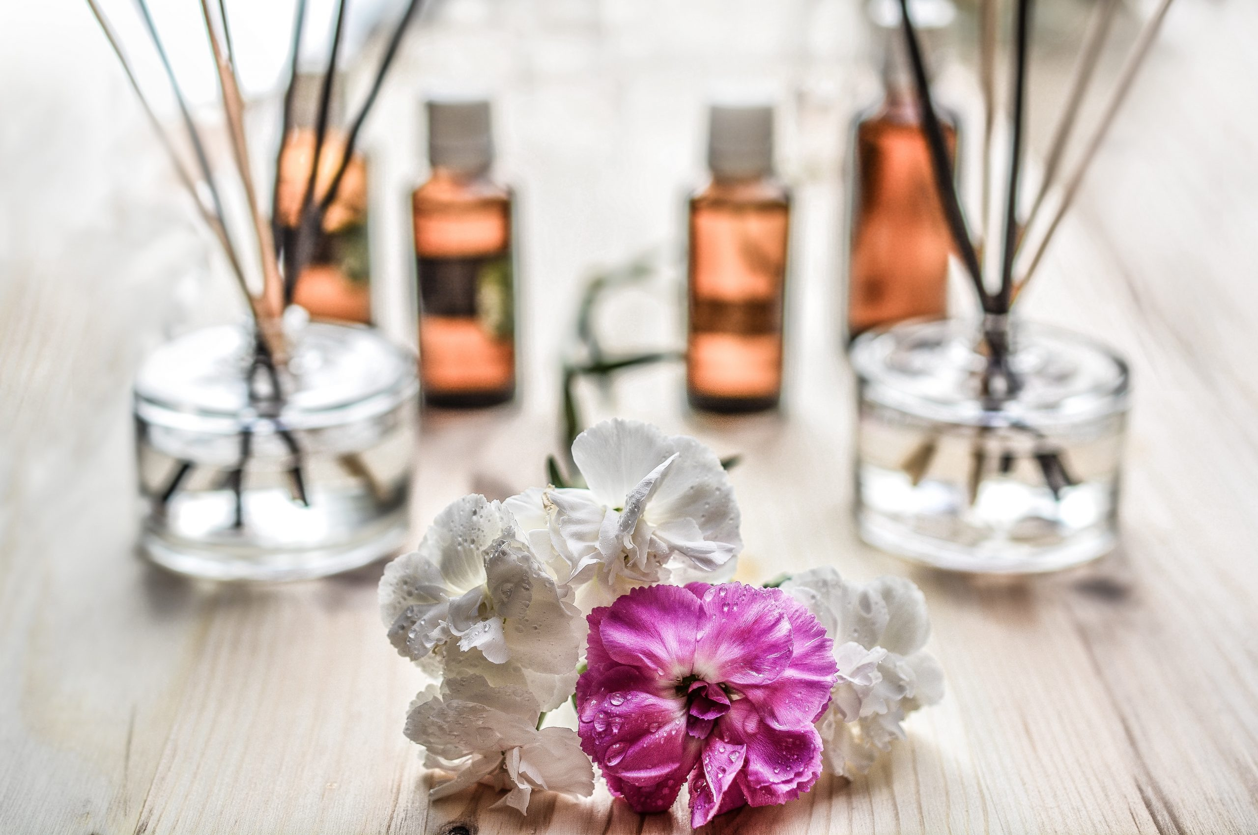 One purple and three white flowers on a light brown table with glass vases that have reed sticks in them and four bottles with essential oils