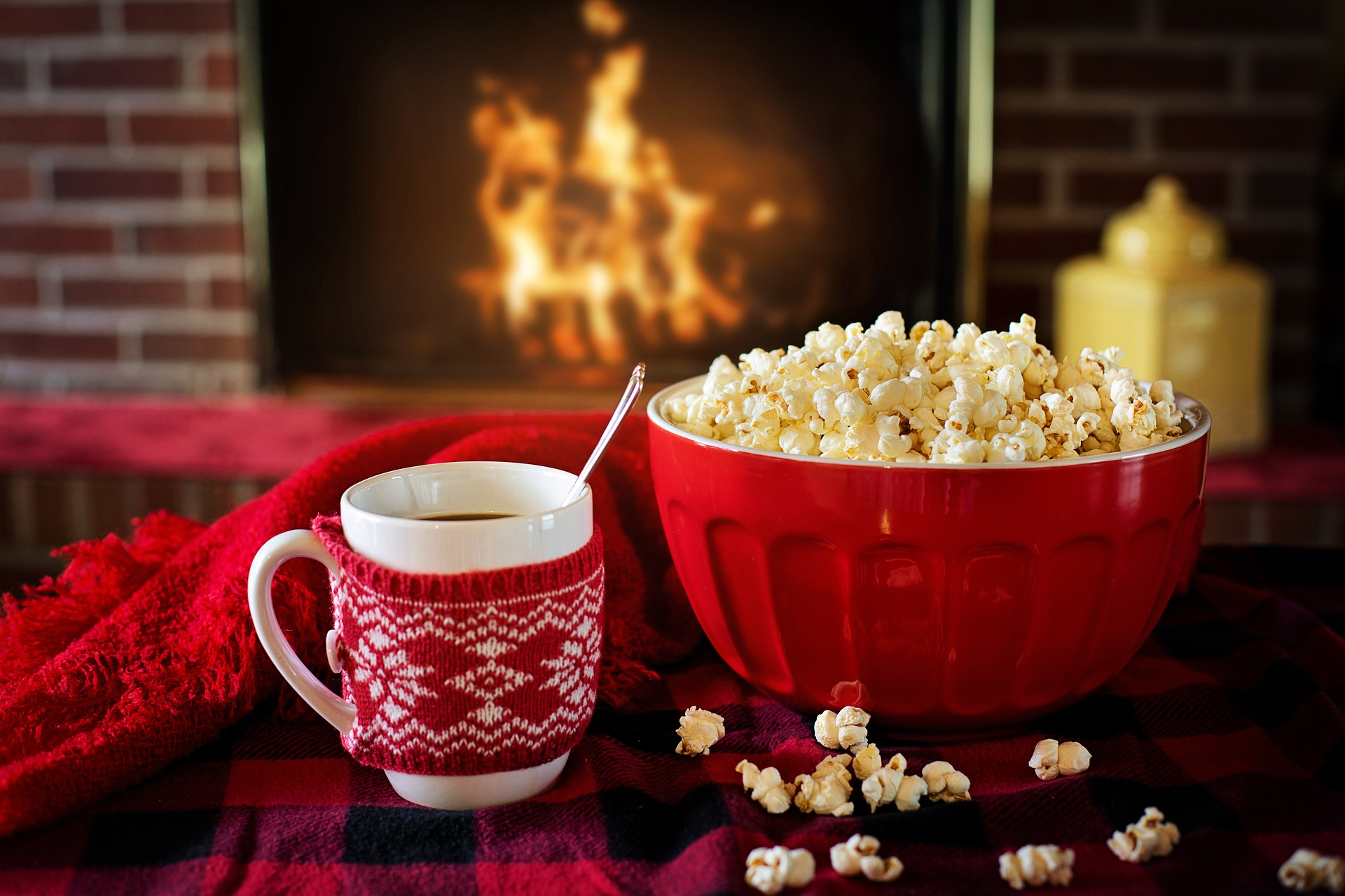 A mug of hot chocolate with a bowl of popcorn by the fireplace