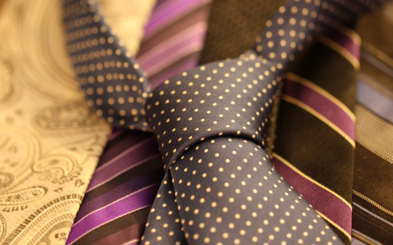 A black shirt tie with yellow polka dots, placed on top of other ties