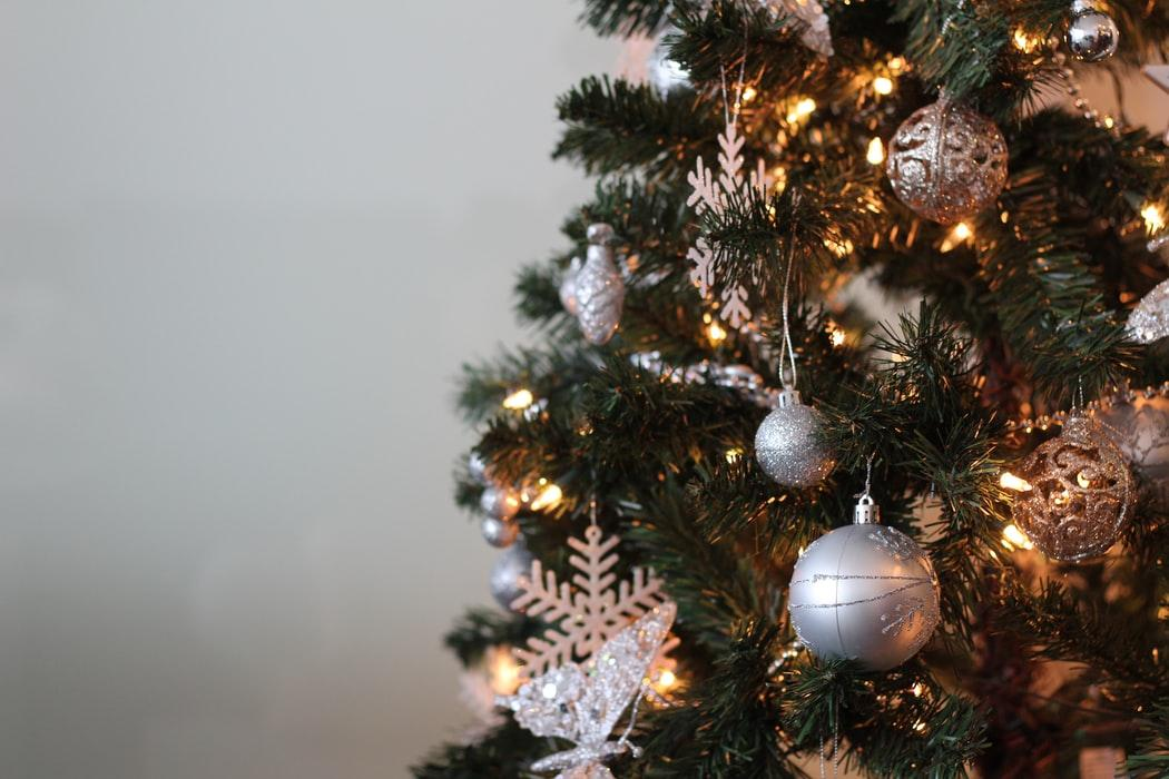 White baubles and snowflakes hanging from a Christmas tree.