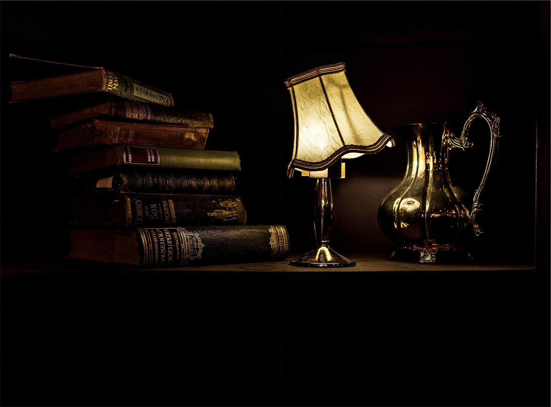 A lit desk lamp, hardcover books and a teapot on a desk.