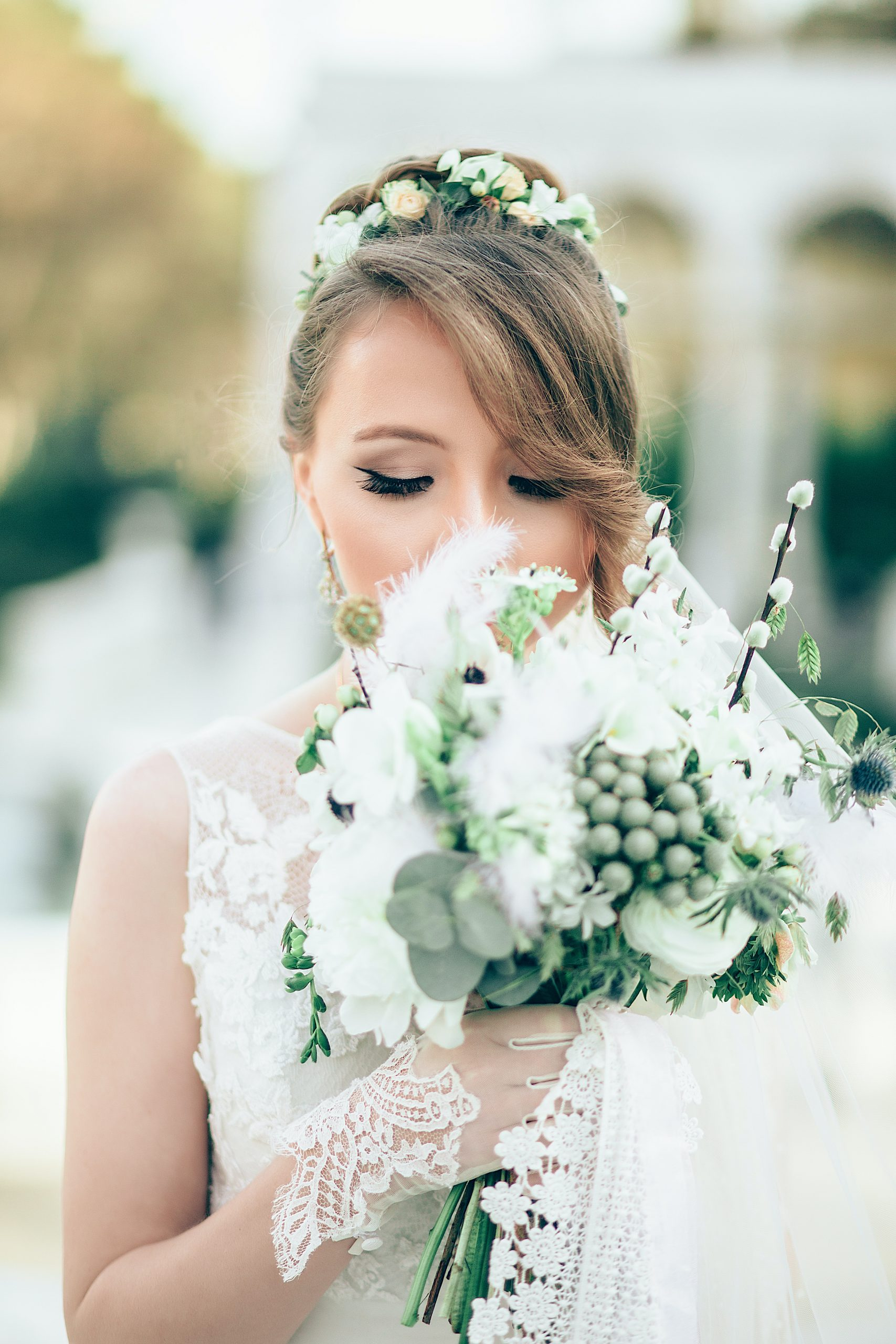 A bride dressed in white posing for a photograph with a bunch of flowers