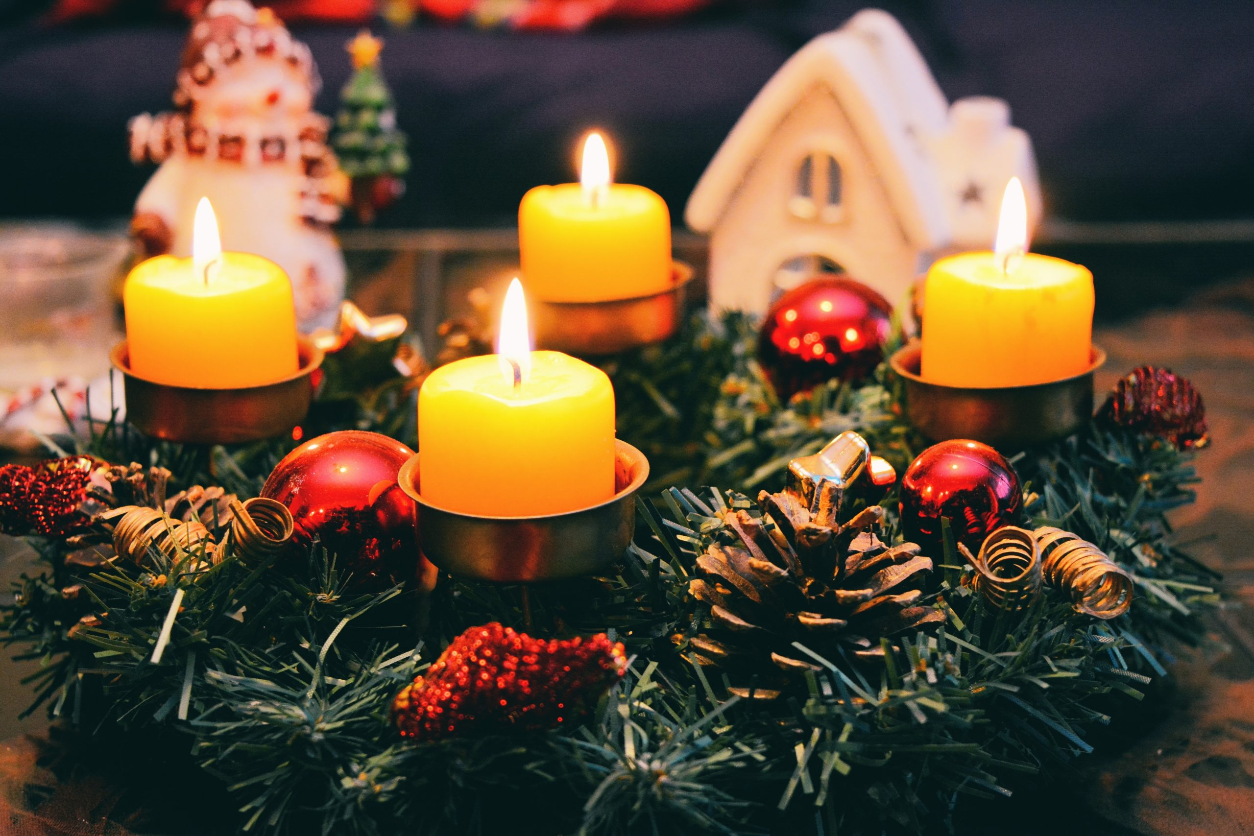 Four yellow candles sitting on top of a Christmas tree decoration featuring pinecones and baubles.