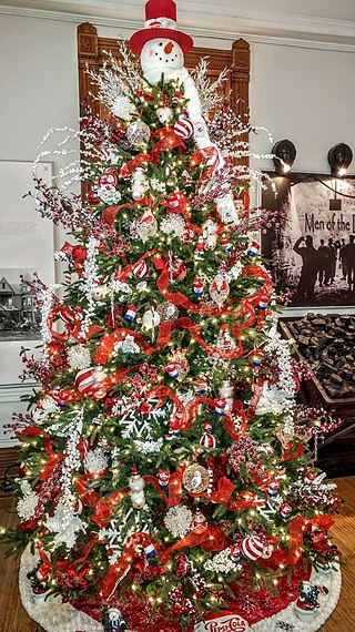 A Christmas tree adorned with a variety of red decorative elements and topped off with a snowman with a red nose and red hat.