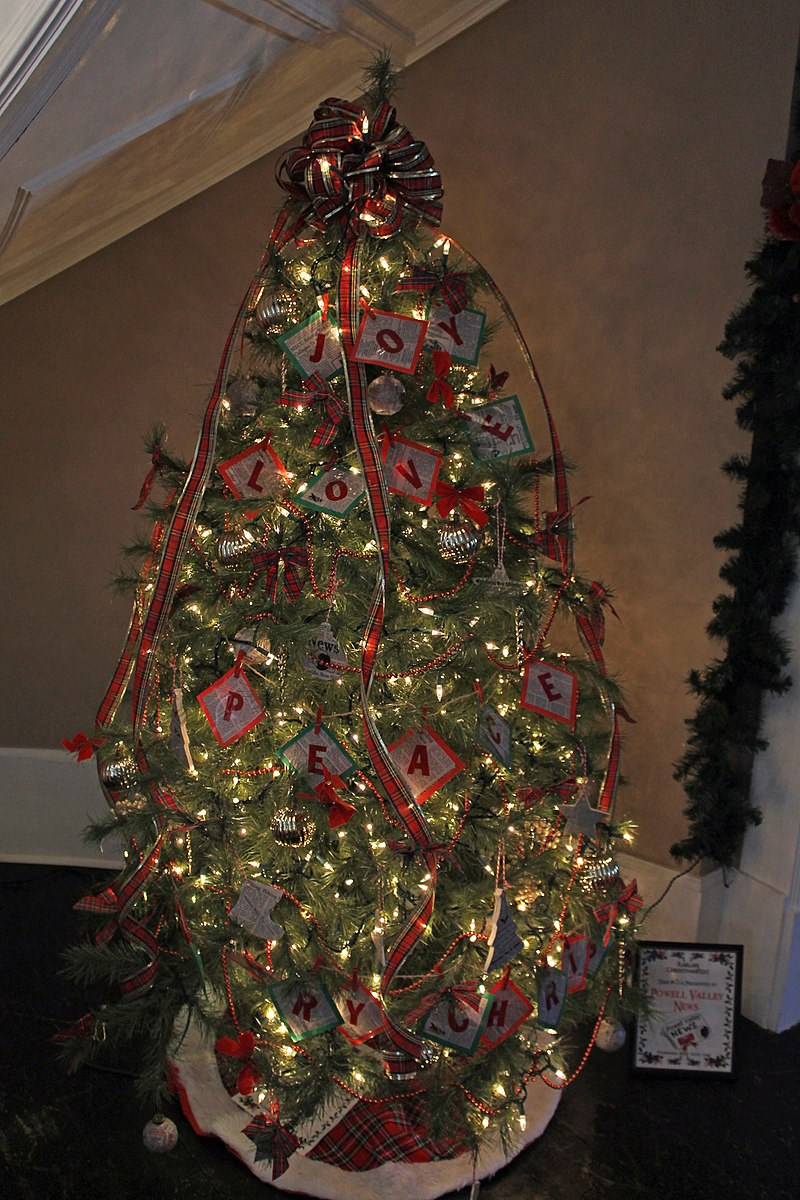 A Christmas tree featuring decorative lights, plaid, and messages that capture the Christmas spirit.