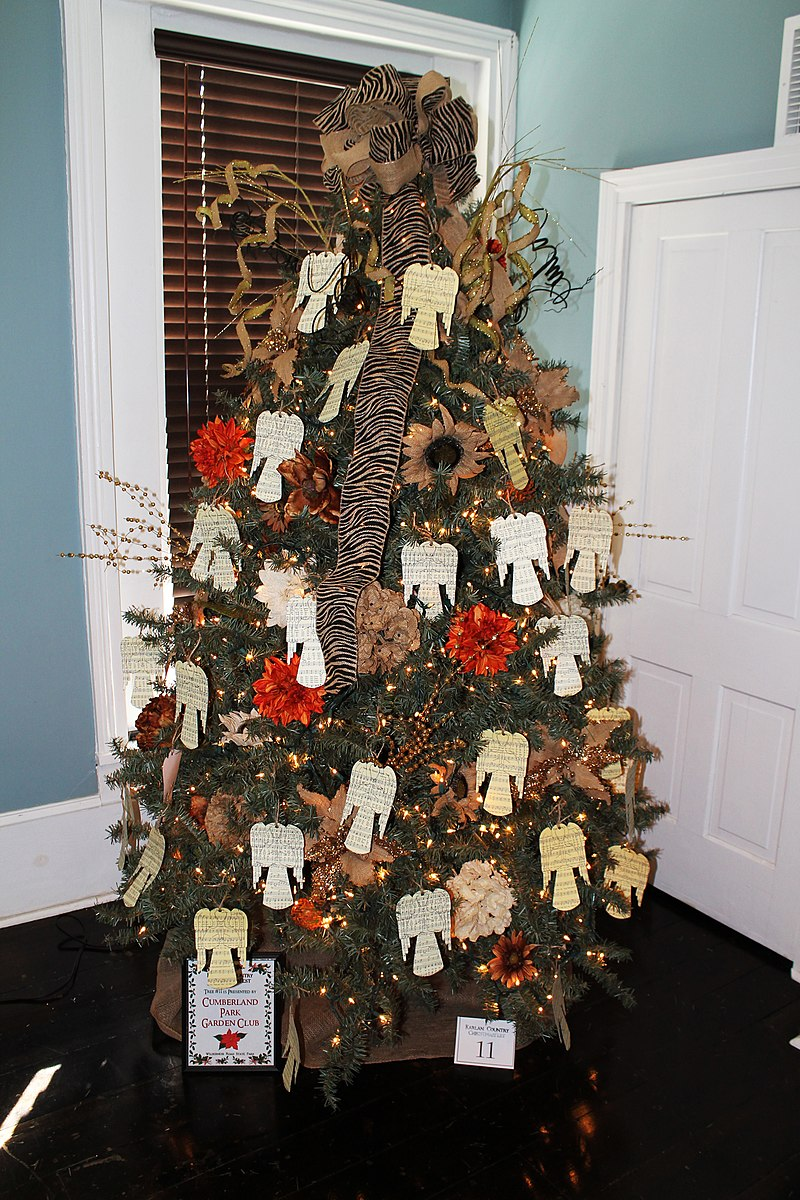 A Christmas tree decorated using a variety of red and brown flowers and other decorative elements that give it a rustic charm.