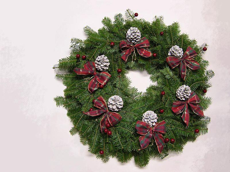 A colorful buffalo plaid Christmas wreath decorated with flowers, cherries, greenery, pine cones, and ribbons.