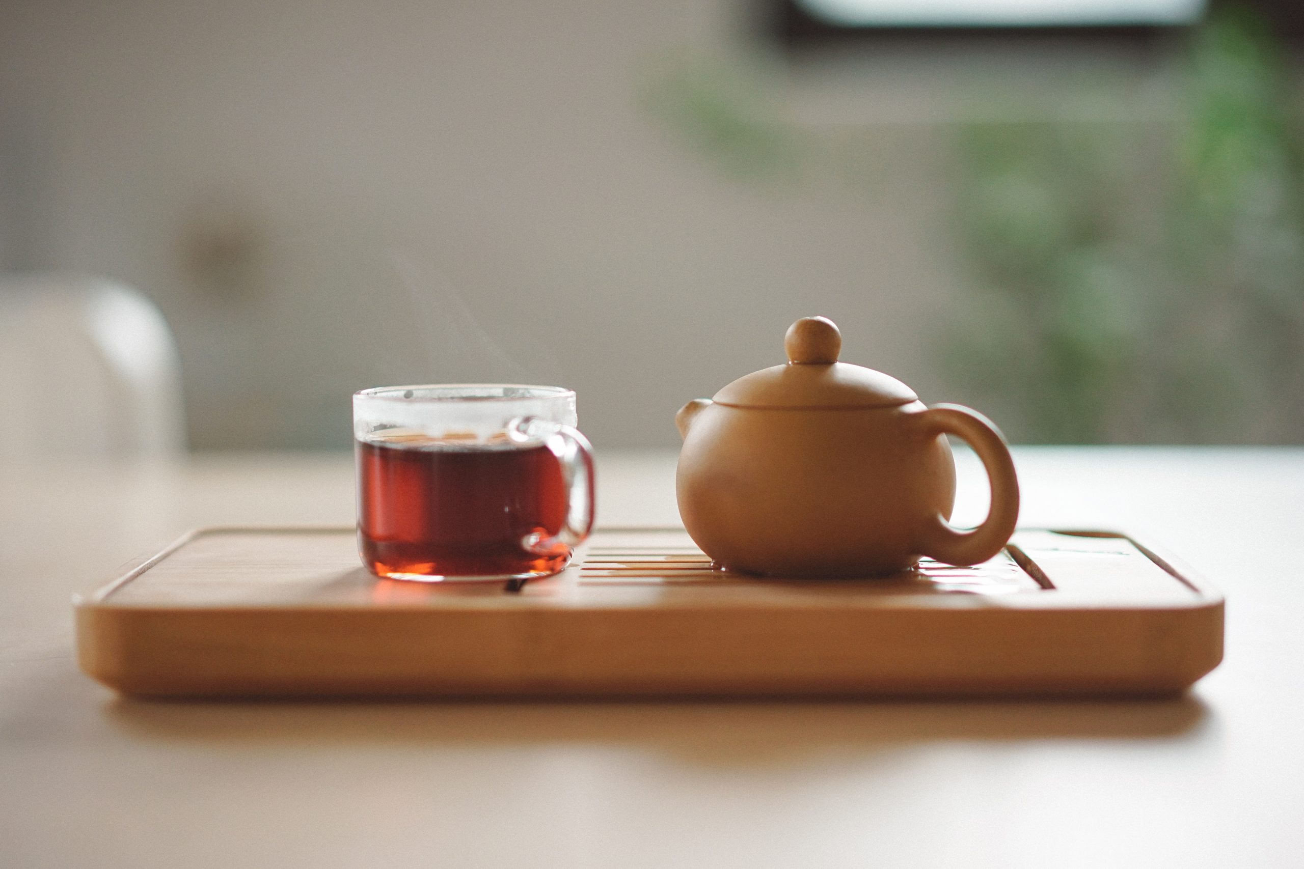 A cup of tea and a kettle placed side by side on a wooden tray, which is placed on a table.