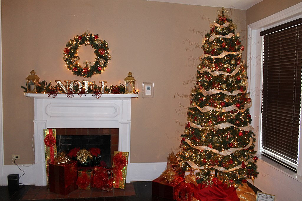 A Christmas tree placed in the corner of a room beside a decorated fireplace with numerous gifts.