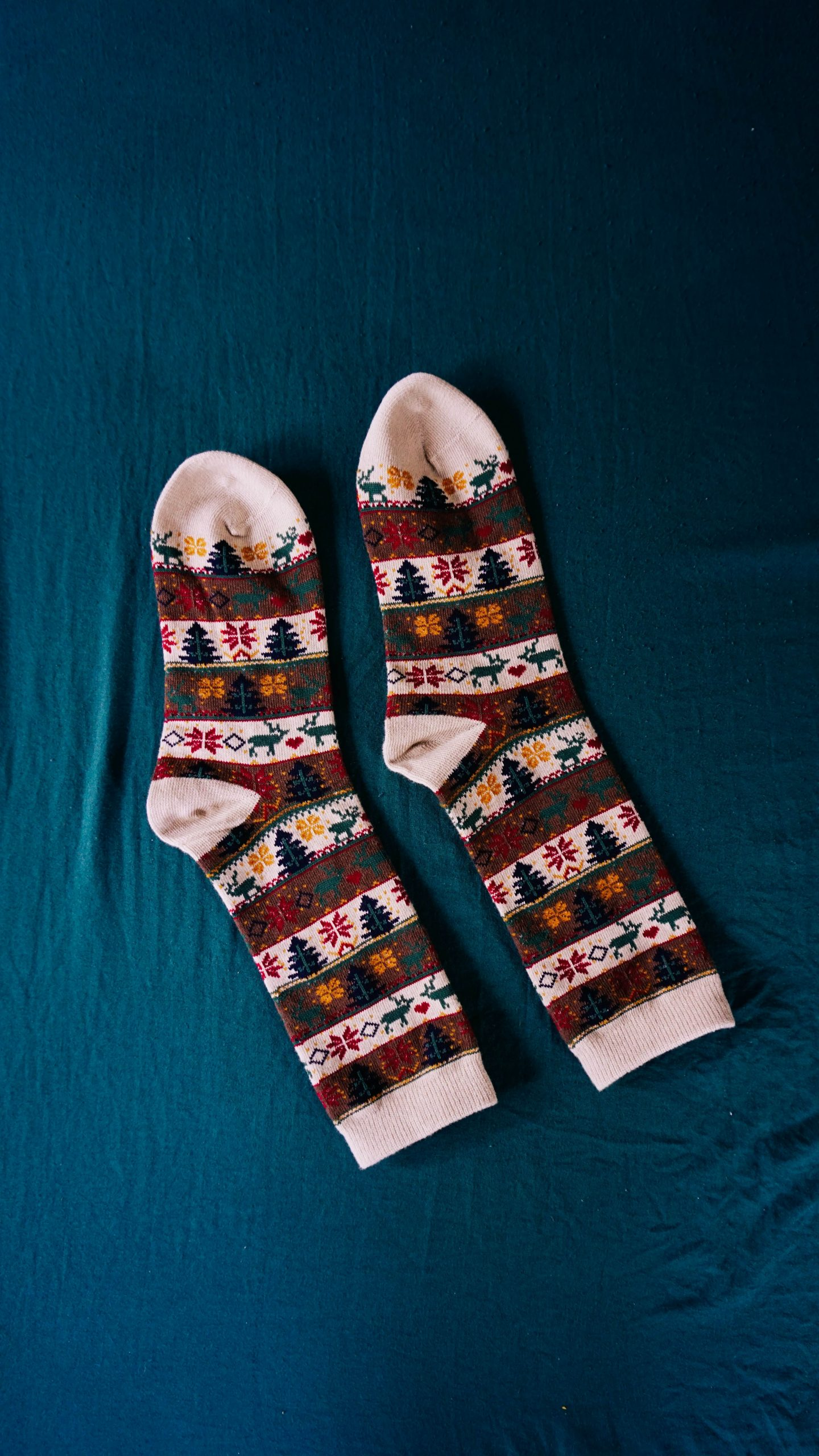 A pair of Christmas socks with imprinted Christmas trees and reindeer.