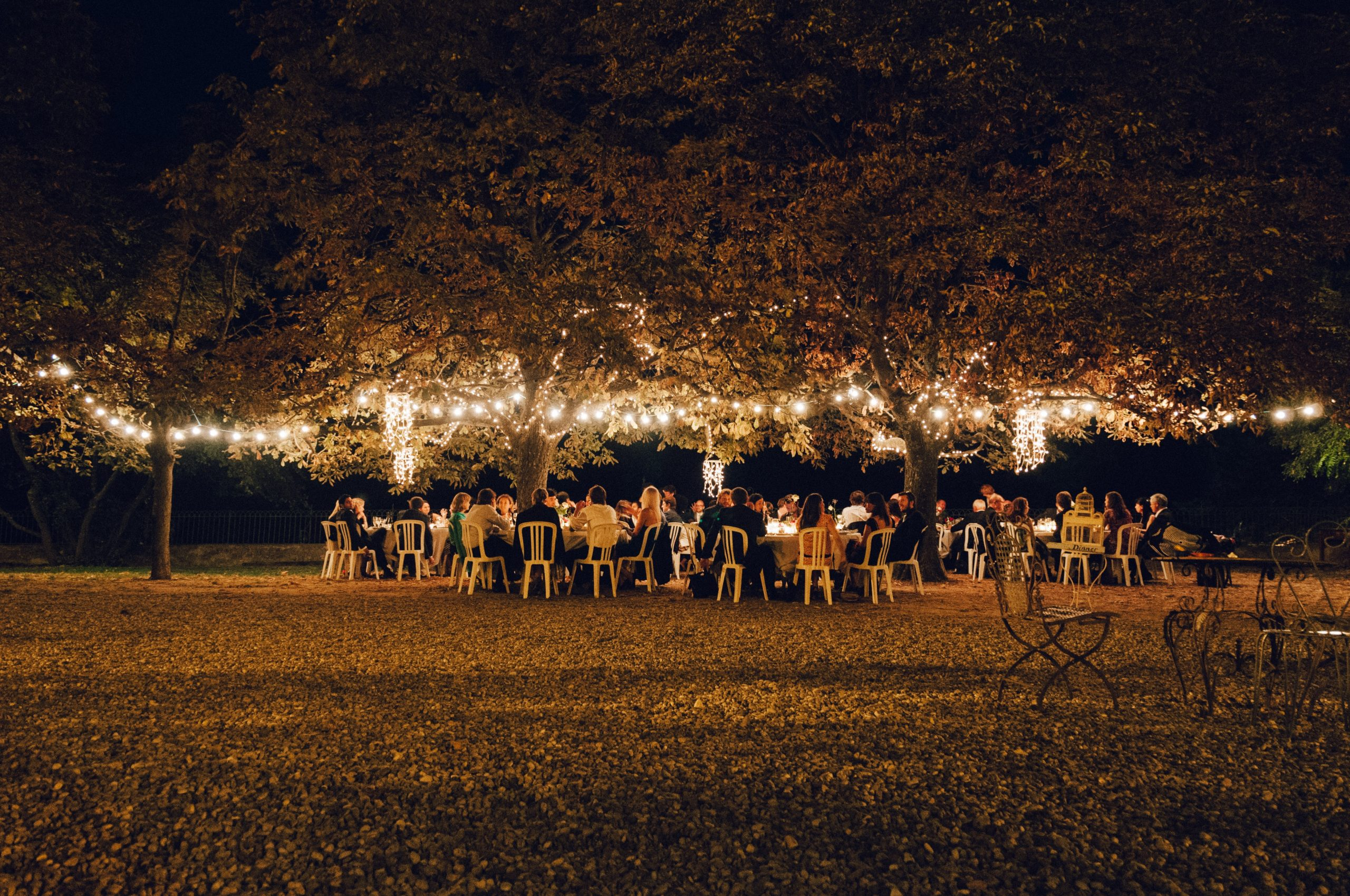 An outdoor wedding venue with lighting during the evening