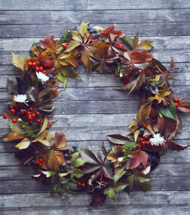 A wreath made with fall leaves and berries of different colors