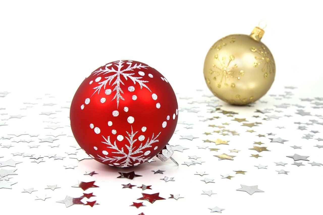One red and one golden artistically designed Christmas bulb against a white background with silver stars beneath them