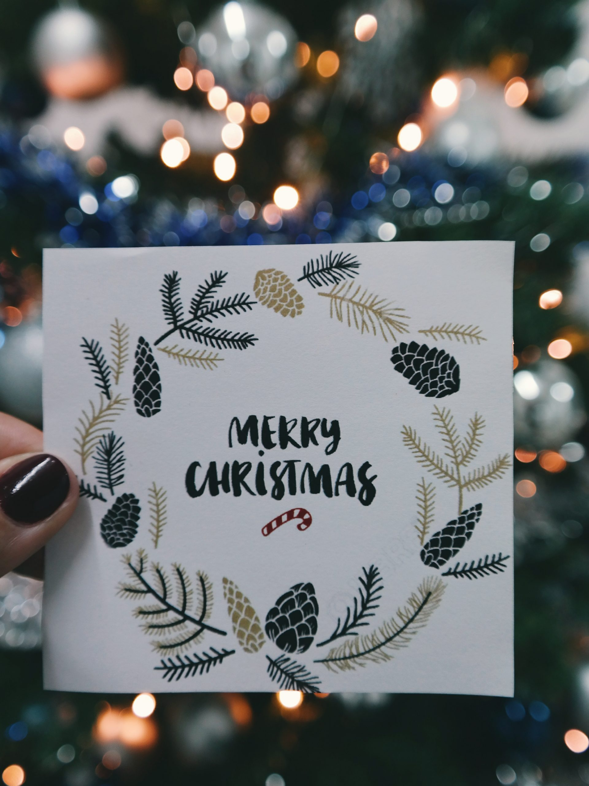 A wallpaper of a hand holding a Christmas greeting card