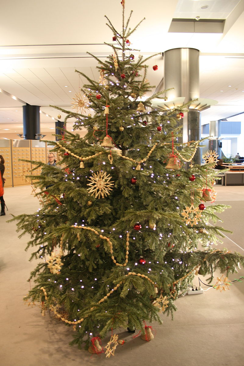 A Christmas tree that is decorated mostly with red balls, golden bells, stars and strings, and white lights.