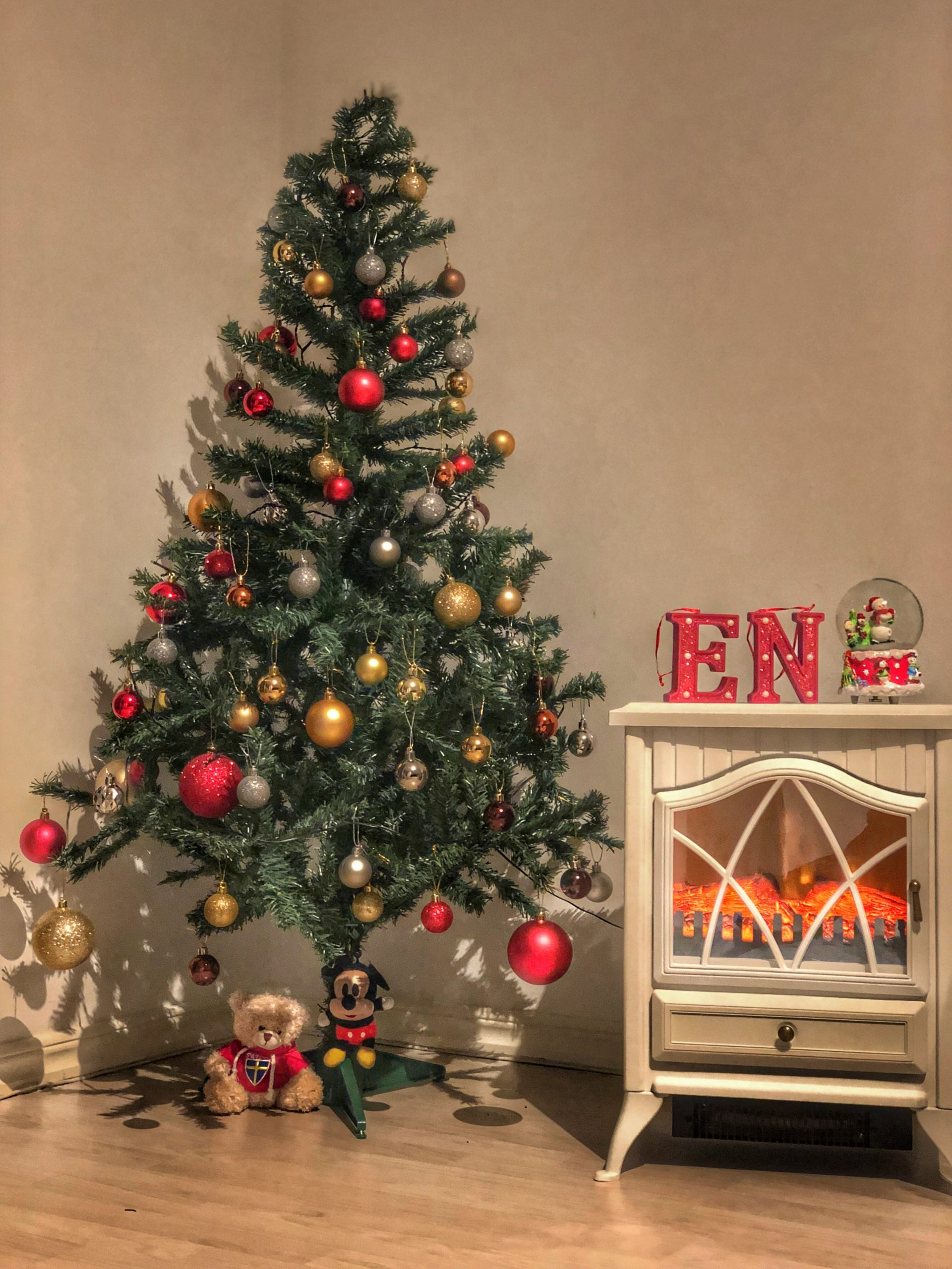 A Christmas tree decked with ornaments placed beside a table.