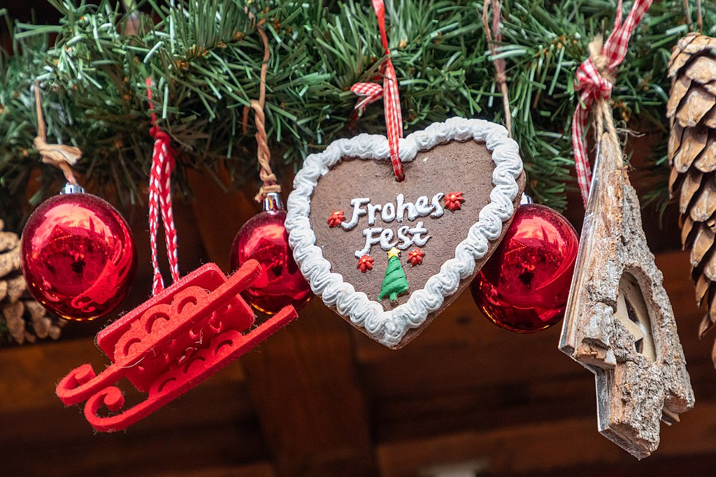 Red decorative balls, a red sleigh, a brown heart, and a wooden imitation of a Christmas tree.