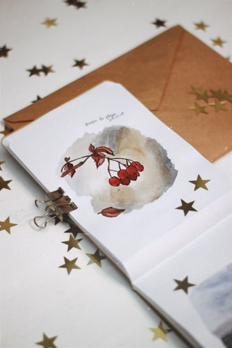 Clipped pages of a diary with a leaf and bunch of red berries drawn along with golden stars stuck on it set against a brownish gold envelope and white background with more golden stars on it
