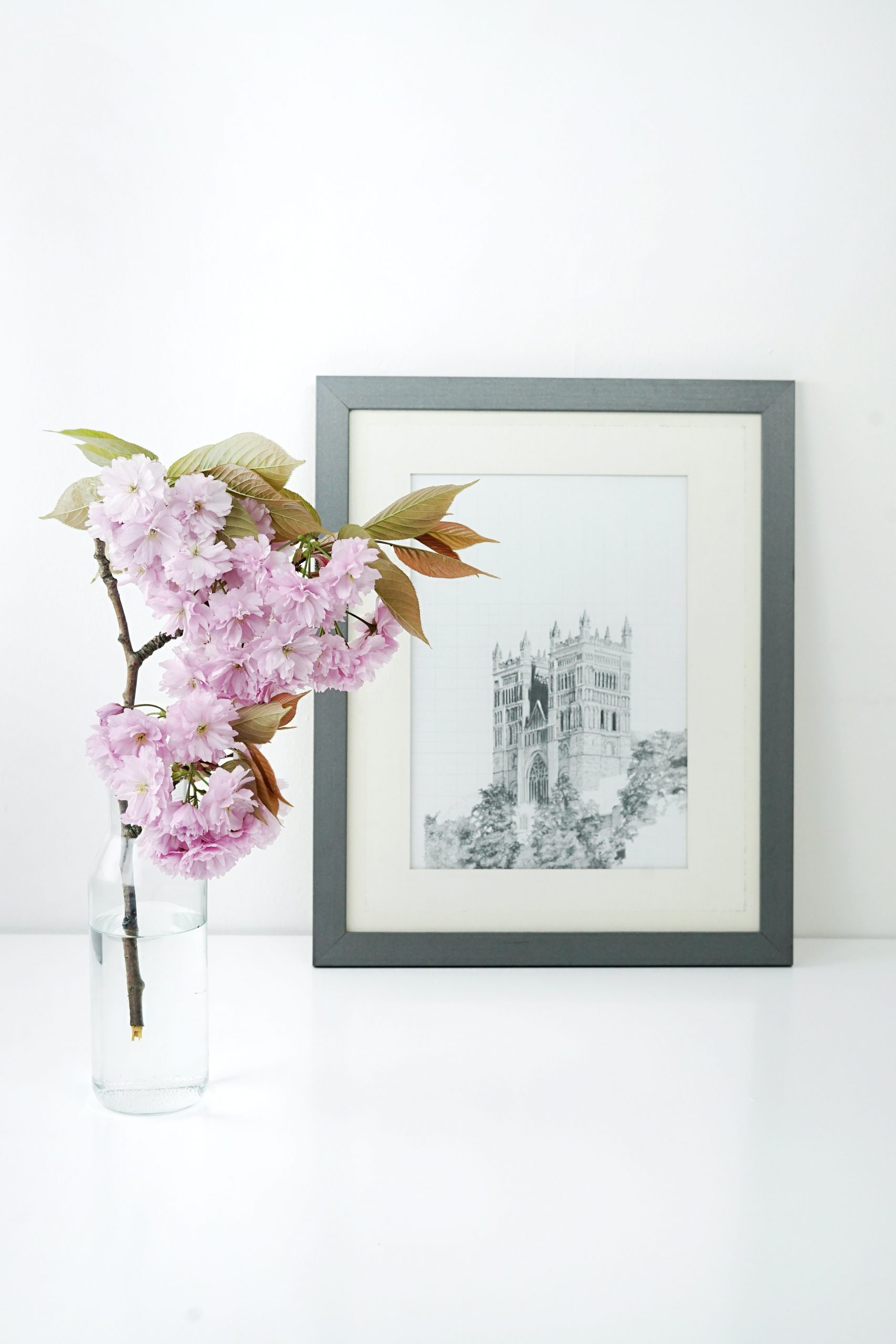 Flowers placed inside water in a glass bottle and a black and white photo of a monument in the background.
