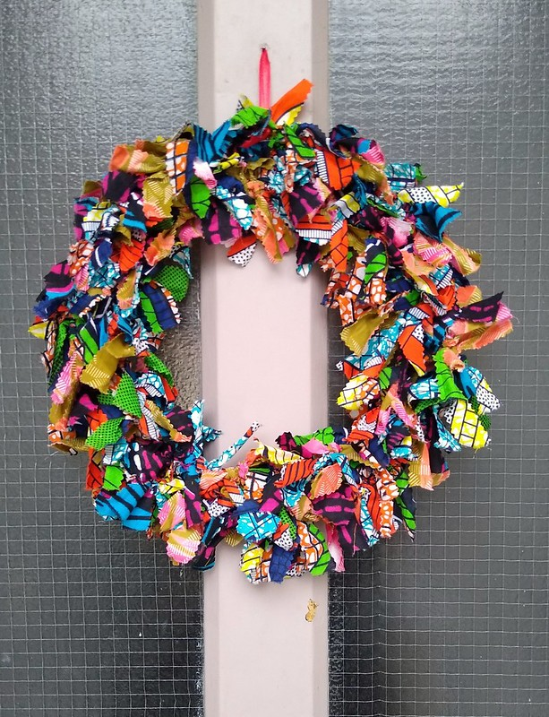 A homemade fabric colorful Christmas wreath on the front door