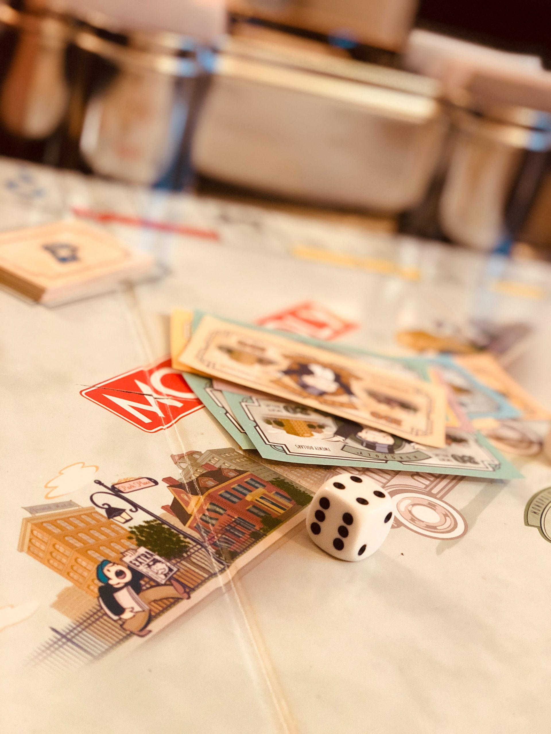 Monopoly game board, cards, and dice on a table.
