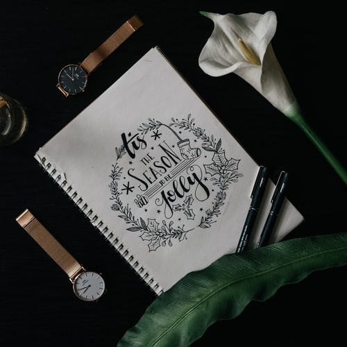 "An open journal page that reads, ""Tis the season to be jolly"" against a black background with two watches, two pens, and a flower."