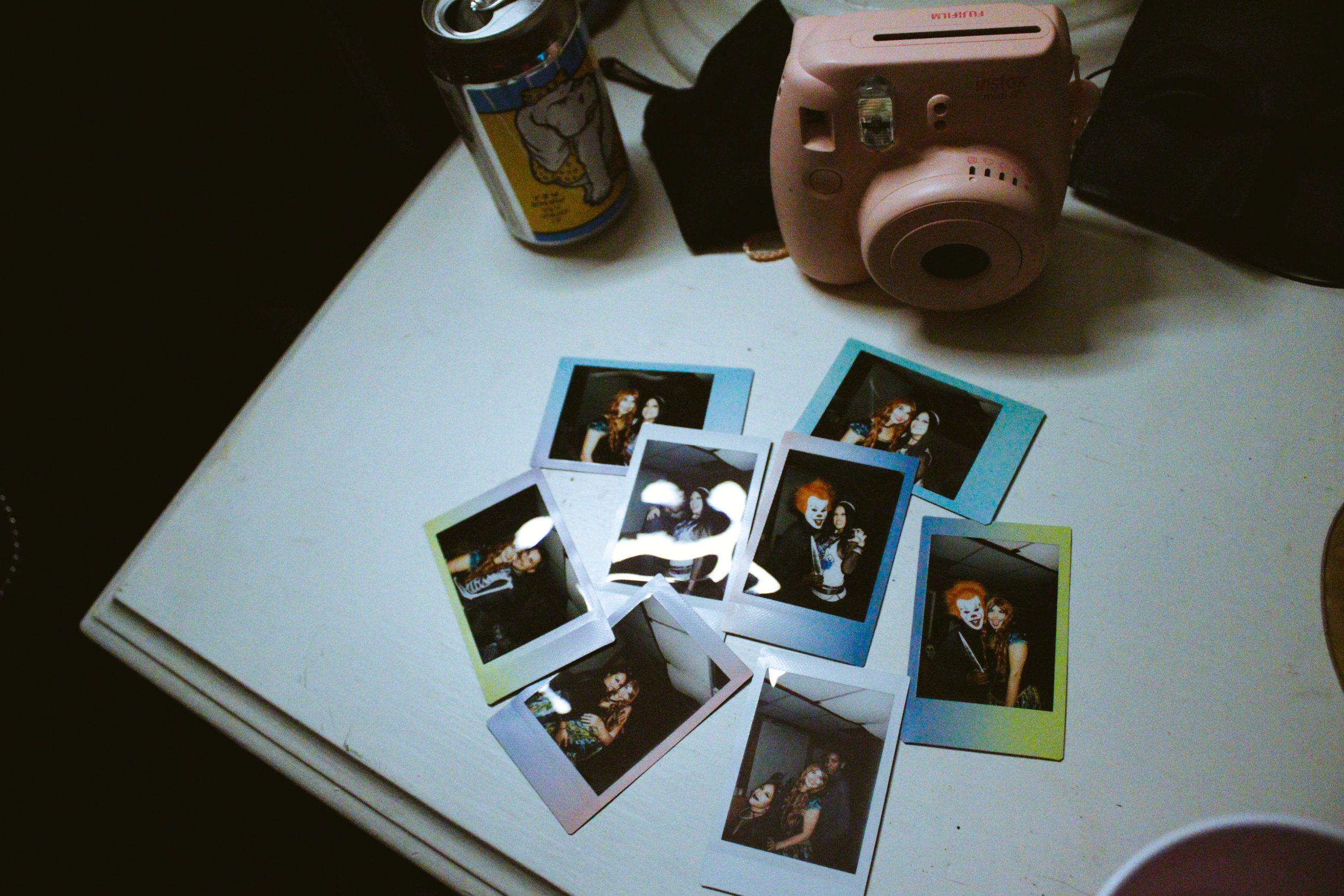 A pink polaroid camera, a beverage can, and photos on a table.