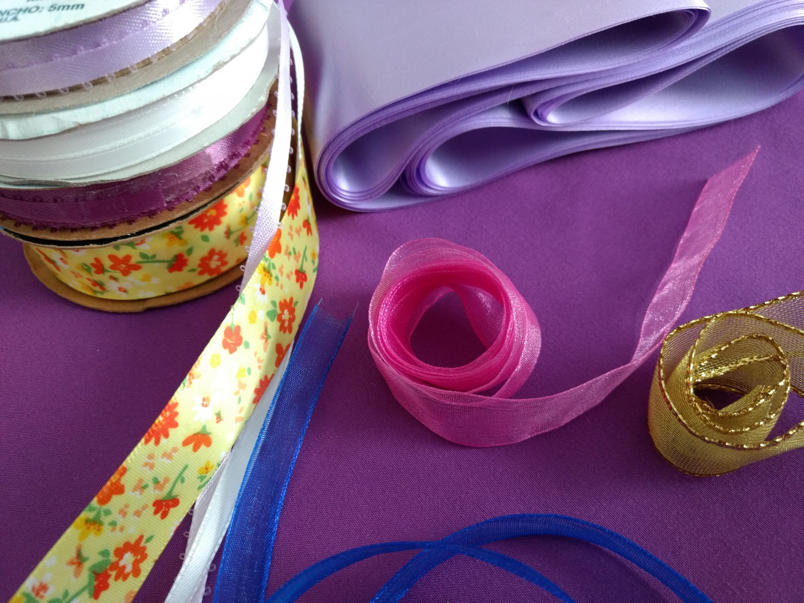 A white, purple, blue, gold, pink, and flowery ribbon roll along with a purple sheet, set against a purple background