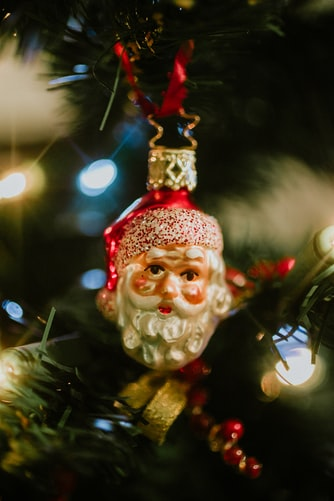 Santa Claus ornament hanging on a Christmas tree