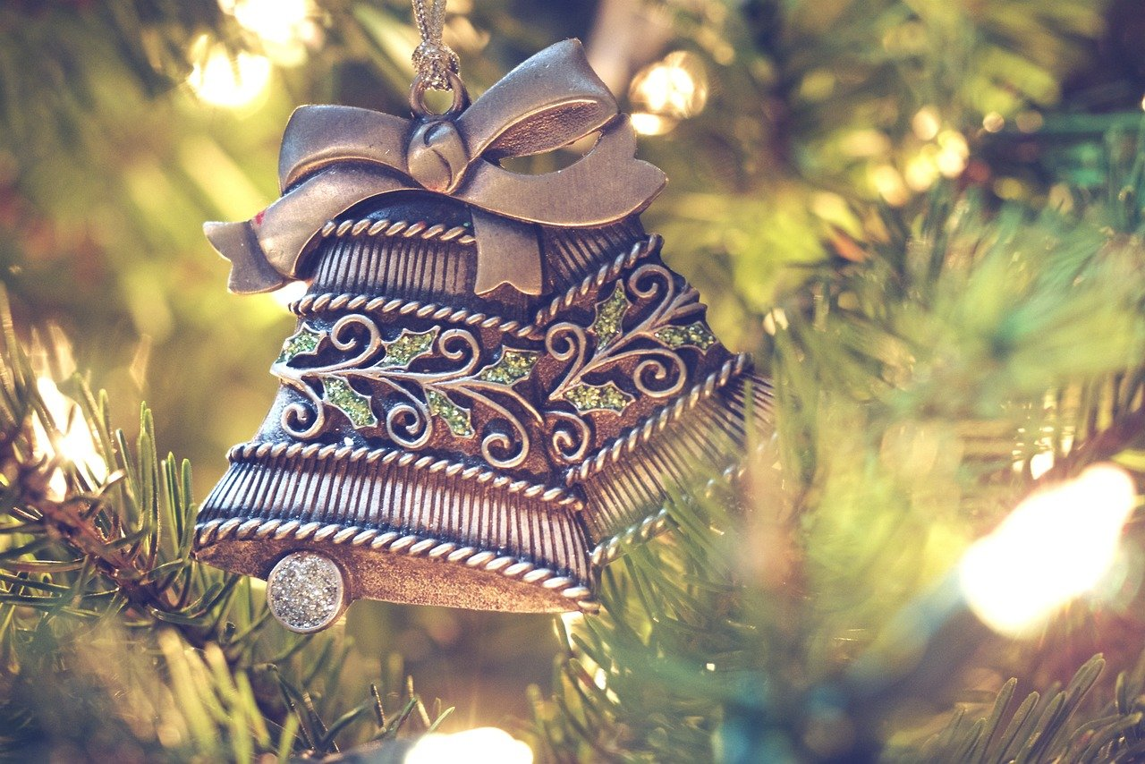 Two silver Christmas bell ornaments on a tree