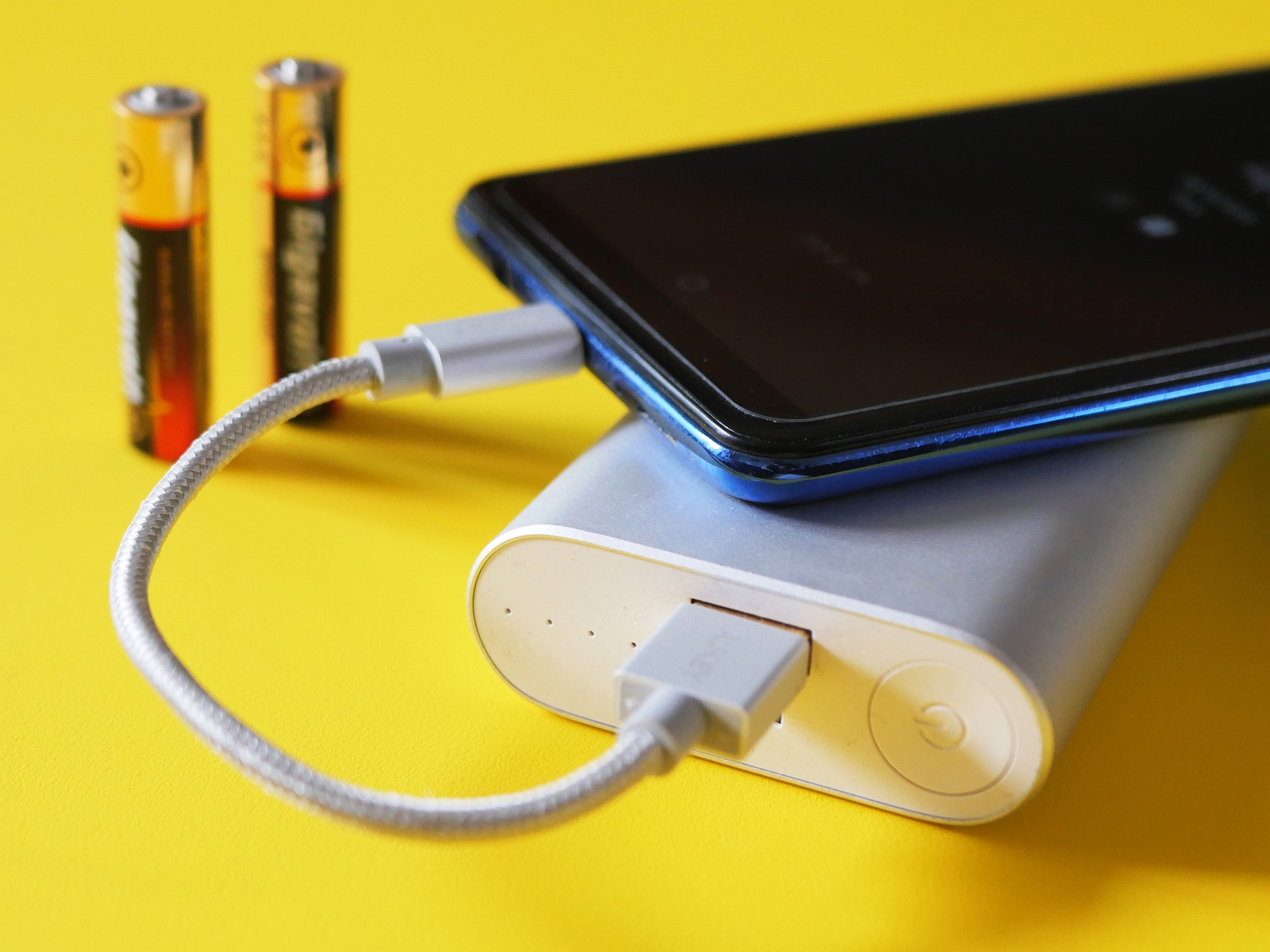 A smartphone getting charged from a white power bank.