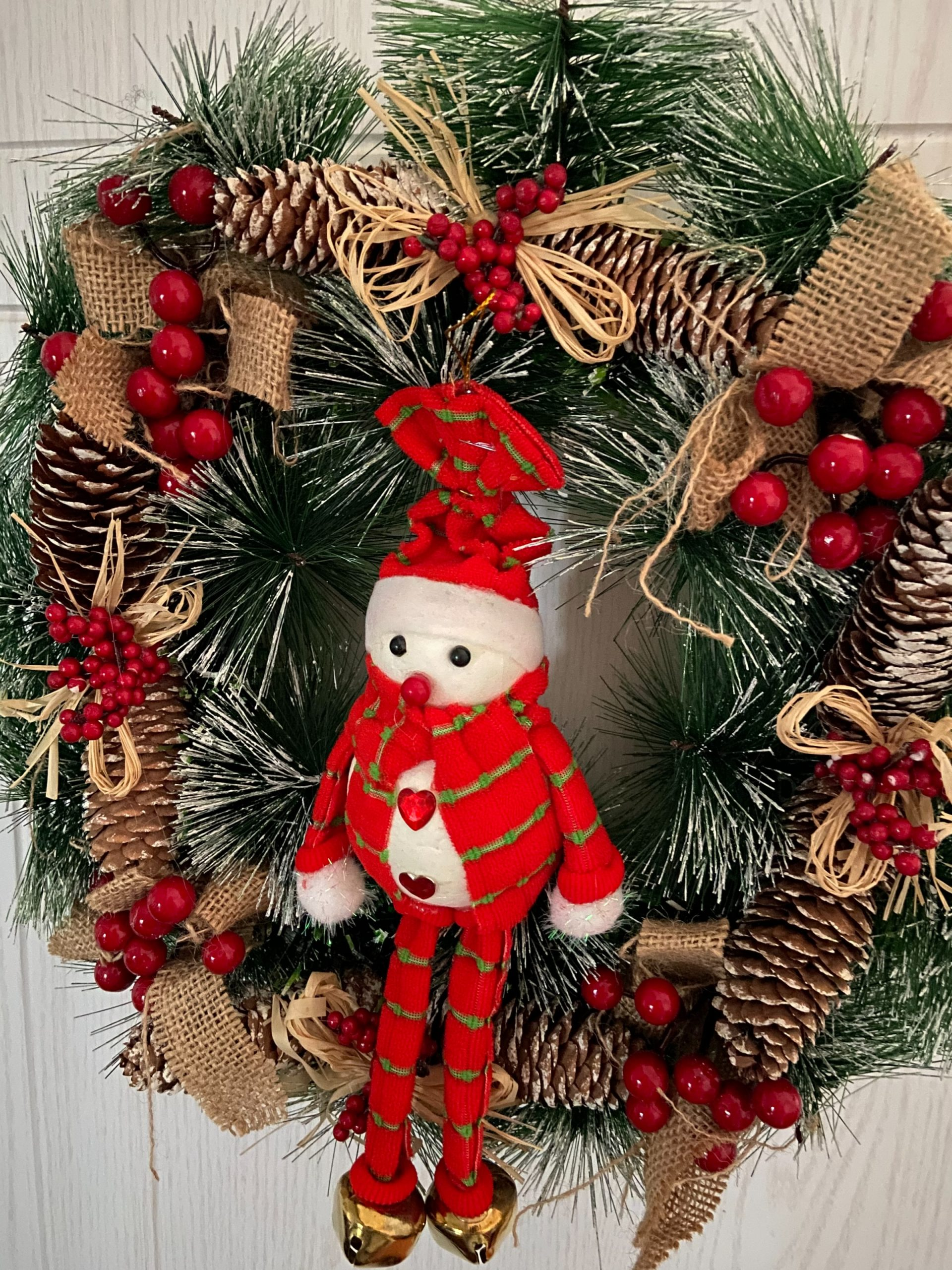 Red snowman hanging on a rustic christmas wreath