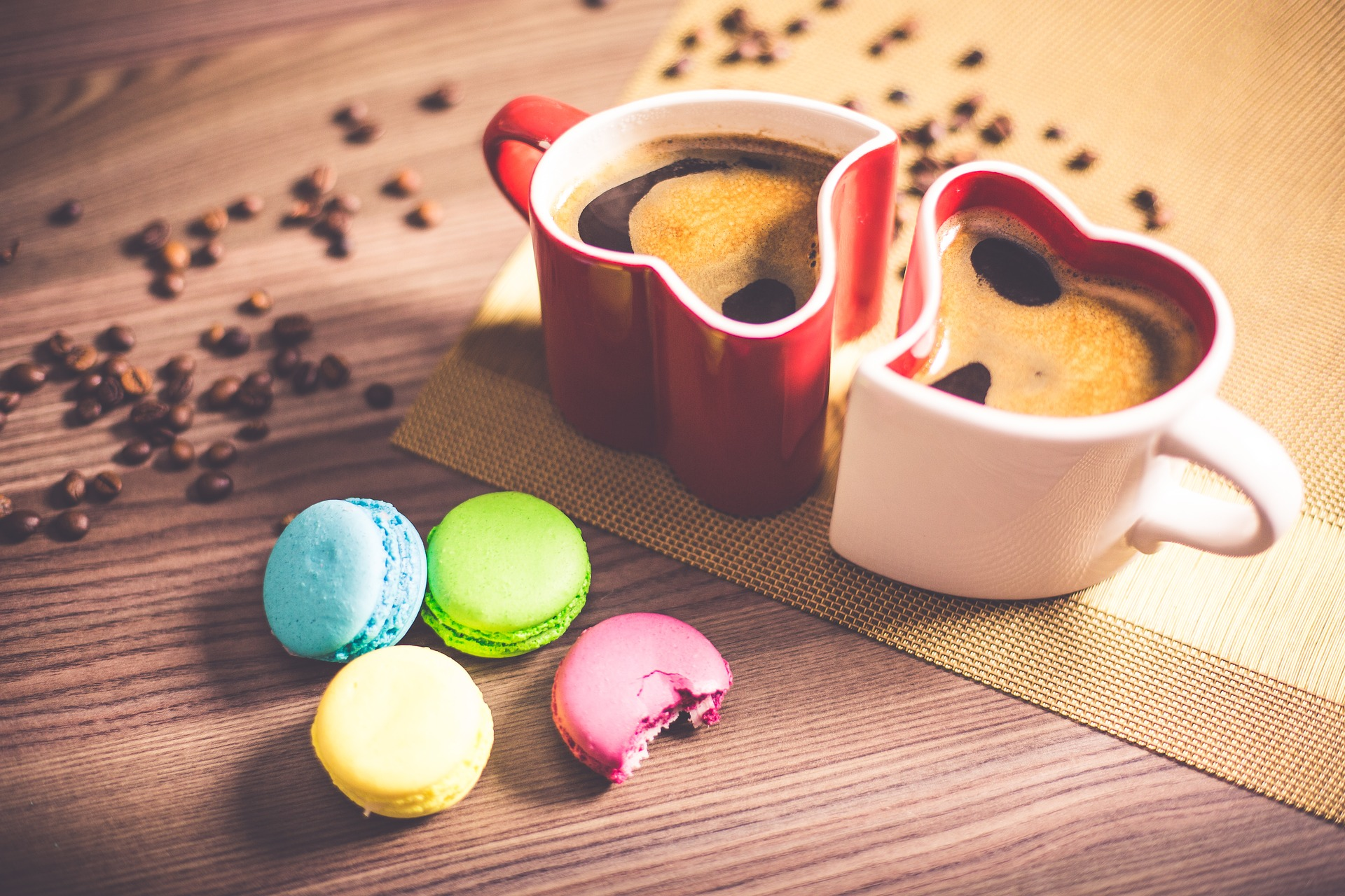 Two heart-shaped coffee mugs with hot coffee, macrons and coffee beans on a table.