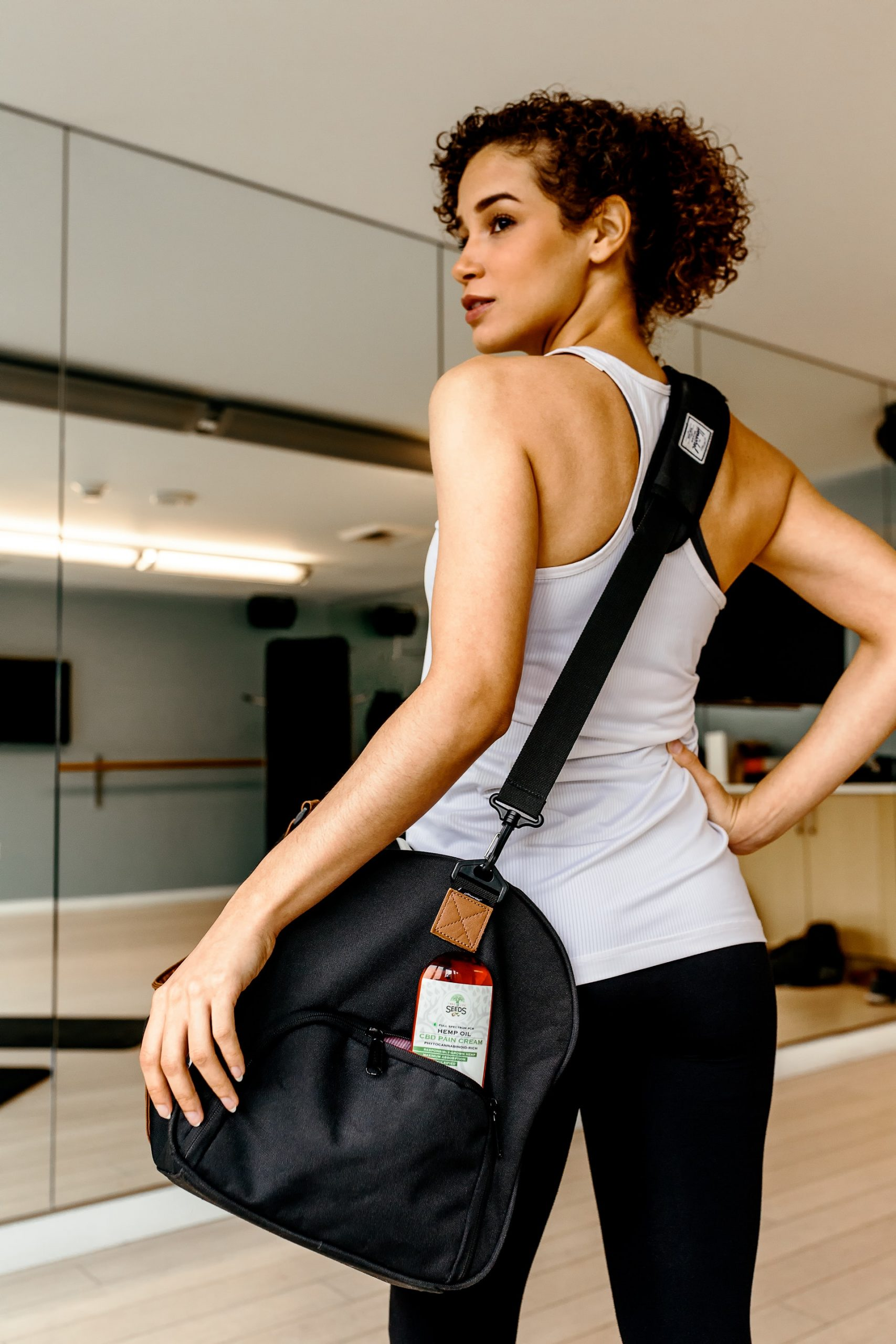 A woman in a gym with a gym bag.