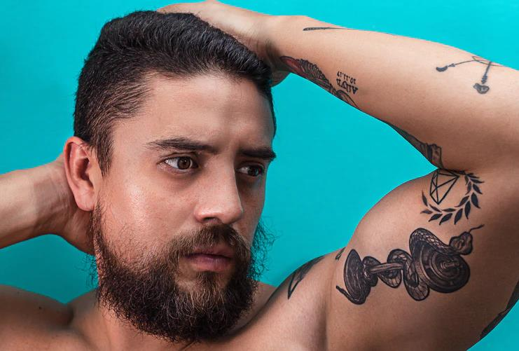 A bearded young man shows the wrapped around arm snake tattoo inked on his left bicep