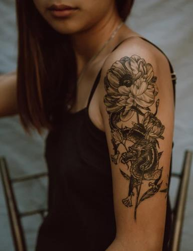 A lady showing her rose and snake tattoo on her left arm.