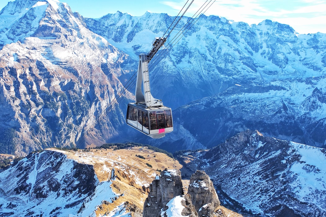 Image of a cable car moving through the high rises of Switzerland, surrounded by stunning beauty of mountains covered in snow.